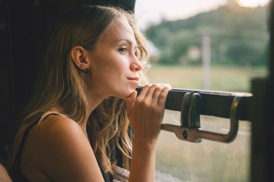Mood atmospheric lifestyle portrait of young beautiful blonde hair girl looking out of window from riding train. Pretty teen enjoying beauty of nature from moving train car in summer. Travel concept