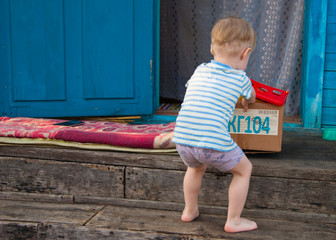 Early spring, the village, a little blond boy of three years old in a T-shirt and panties pulls a box of toys out of the house into the street