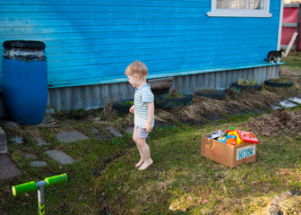 Early spring, the village, a little blond boy of three years old in a T-shirt and shorts walks in the yard barefoot on the young grass.