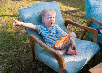 In the early spring, in the village, a little blond boy sits in a blue plush armchair outside in the courtyard of his house and eats snacks, on his face are a variety of emotions