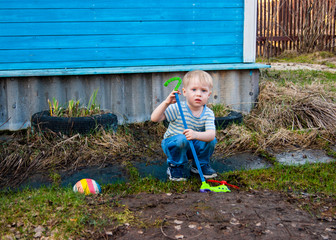 In the early spring, in the village, a little blond boy of three years old rolls a green toy airplane on a stick in the yard of his house