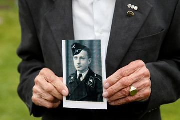 German World War II veteran Konrad Scheucher poses with a picture of himself as a soldier at La Cambe German war cemetery in La Cambe in Normandy as France prepares to commemorate the 75th anniversary of the D-Day