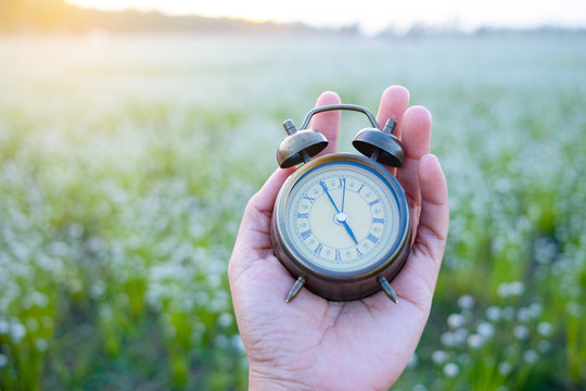 Alarm clock put on hand with field grass background.