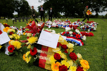 German army soldiers prepare wreath of flowers at La Cambe German war cemetery during a remembrance ceremony in La Cambe in Normandy
