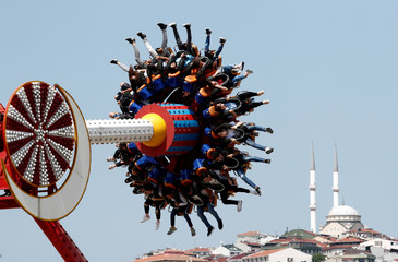 People enjoy a ride in an amusement park as they celebrate the second day of the Muslim holiday of Eid al-Fitr in Istanbul
