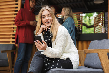 Smiling excited teenager sitting outdoors