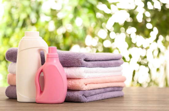 Stack of clean towels with detergents on table against blurred background. Space for text