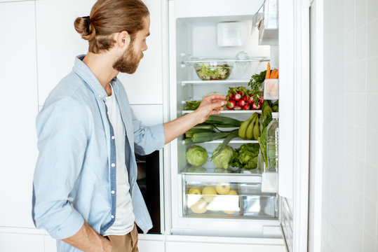 Young vegan man choosing what to cook, taking fresh vegetables from the refrigerator at home