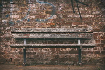 old wooden bench against a brick wall with graffiti.