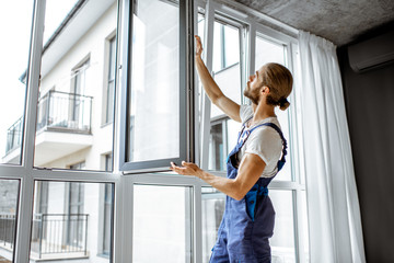 Workman in overalls installing or adjusting plastic windows in the living room at home Wall mural