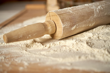Rolling pin on pastry board sprinkled with flour on wooden  table