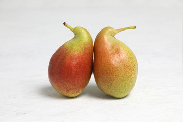 Ugly vegetables , two ripe pears of bizarre shape ,are leaning . on a white background . the fruits are like penguins .