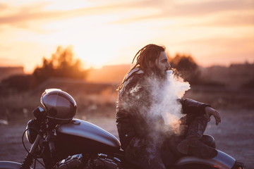 Side view of man smoking electronic cigarette on motorbike during sunset