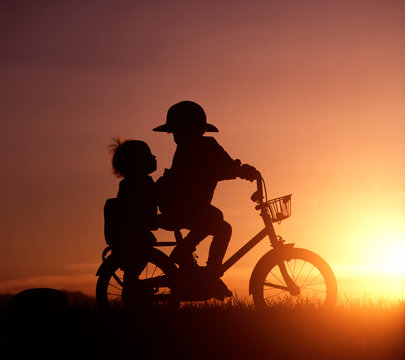 Silhouette of siblings riding bicycle during sunset