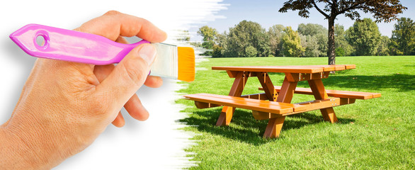Hand drawing a picnic table on a green meadow - concept with copy space