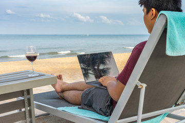 Freelancer working with laptop , red wine on beautiful summer beach
