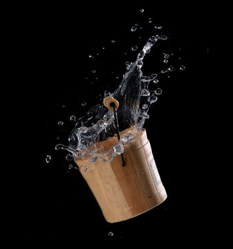 Wooden bucket with water splash or explosion flying in the air isolated on black background,Motion blur