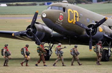 Paratroopers in World War II uniforms walk to their Dakota aircraft prior to take-off from Duxford airfield as they head to Normandy in France