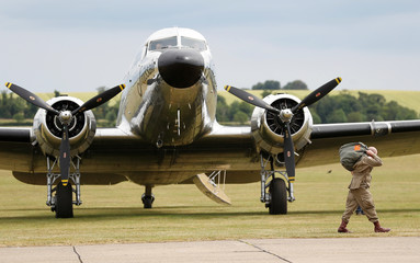 A paratrooper in World War II uniform walks past a Dakota aircraft before flying to Normandy in France