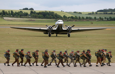 Paratroopers in World War II uniforms walk past a Dakota aircraft before flying to Normandy in France
