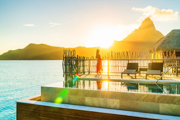 Wall Mural - Luxury resort high end hotel rich people lifestyle woman tourist relaxing watching sunset on private balcony terrace of overwater bungalow suite in Bora Bora, Tahiti, French Polynesia.