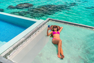 Wall Mural - Luxury resort vacation tourist woman relaxing on overwater catamaran net bed in private bungalow suite using phone taking pictures of summer holiday high end hotel.