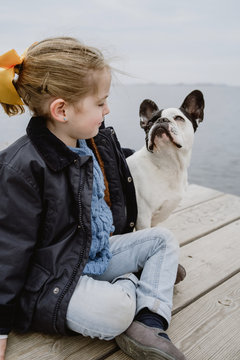 little girl with French Bulldog sitting on pier near sea on dull cloudy day