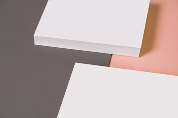 From above composition of heap of empty white business card template on grey and pink background