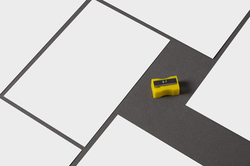 From above composition of empty white cards template and yellow sharpener on grey background