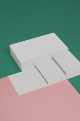 From above composition of heap of empty white business card template on green and pink background