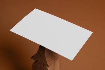 Empty white business card template placed on original wooden stand on brown background