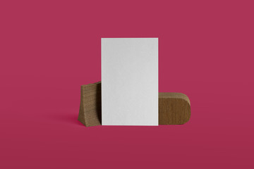 Empty white business card template placed on original wooden stand on pink background