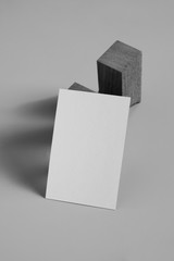 Empty white business card template placed on original wooden stand, black and white picture