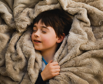Young boy resting with eyes closed while wrapped in a soft blanket.