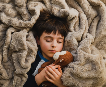 Young sleeping child wrapped in cozy blanket with stuffed toy monkey.