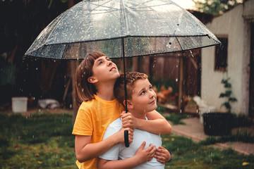 Brother and sister enjoying rain
