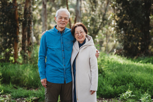 Portrait of senior active couple hugging outside