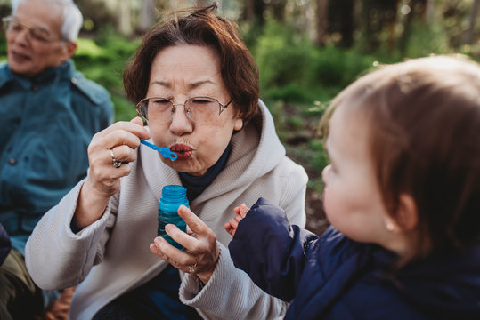 Grandmother blowing bubbles for granddaughter
