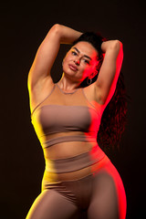 Pretty plump, size plus woman posing on black background in fitness gym.