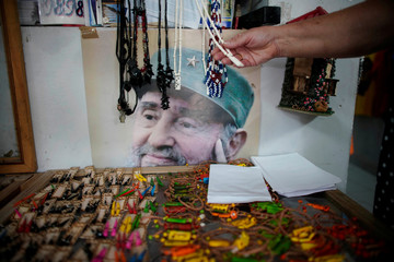 A tourist checks souvenirs in a private shop next to an image of late Cuban President Fidel Castro, in Havana