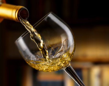 vino bianco versato nel bicchiere,sfondo libreria