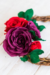 High angle close up of a small wreath with red and purple paper roses.