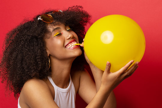 Mulatto model with a lush hairstyle of curly black hair inflates a yellow balloon on a red Studio background