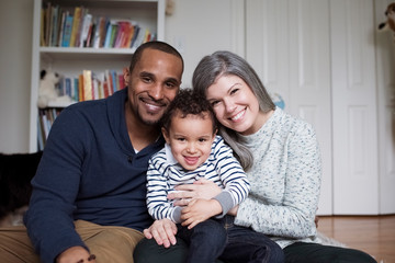 Portrait of happy parents with cute son sitting against wall at home
