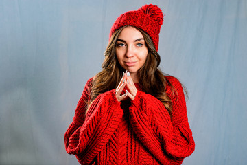 Beautiful, young woman in red knitted sweater and hat on grey background