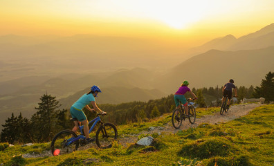 LENS FLARE: Four young travelers ride their mountain bikes downhill at sunrise. Wall mural
