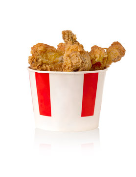 Fried legs and wings on a white background. Chicken wings and legs deep-fried in a cardboard bucket.