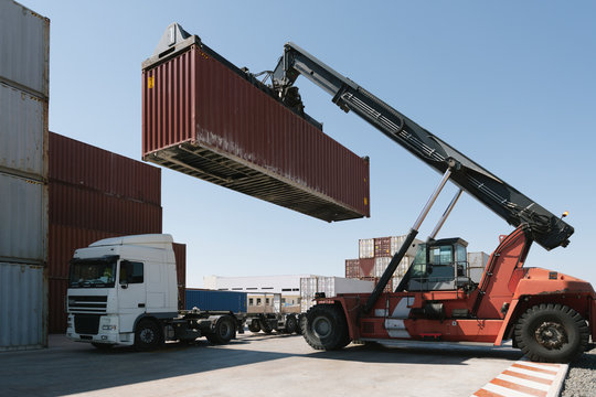 Crane lifting cargo container on truck on industrial site