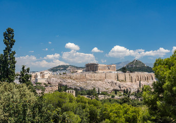 Acropolis and Lycabettus Hill framed by trees from the summit of Lycabettus hill