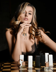 Beautiful woman playing chess with bottles and boxes of auto perfume on dark